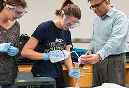 Photo of a teacher helping students in a lab. Links to Closely Held Business Stock